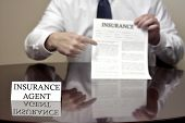 stock photo of contract  - Insurance agent sitting at desk holding insurance contract  - JPG