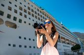 foto of passenger ship  - Young woman tourist photographing near the big cruise liner - JPG