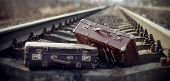 stock photo of old suitcase  - Two old vintage suitcases lie on railway rails - JPG