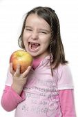 stock photo of missing teeth  - Young girl eating an apple with her new permanent teeth vertical composition - JPG