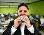 foto of stress-ball  - Young angry businessman while eating balled paper in office. ** Note: Shallow depth of field - JPG
