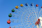 image of color wheel  - Colorful Giant ferris wheel against blue sky background - JPG