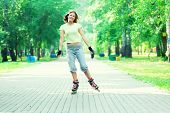 foto of inline skating  - Roller skating sporty girl in park rollerblading on inline skates - JPG