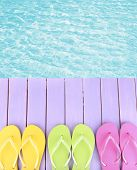 image of beside  - Female flip flops on wooden platform beside sea - JPG