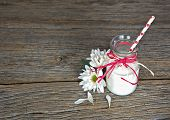 picture of white-milk  - White milk with red and white polka dot straw in retro milk bottle and daisy on rustic wood - JPG