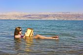 foto of israel people  - beautiful young woman reads a book floating in the waters of the Dead Sea in Israel - JPG