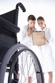 stock photo of rollator  - two women doctors are looking at the card of the patient and a wheelchair is in the frond - JPG