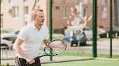 picture of early-man  - young man play tennis outdoor on tennis field at early morning - JPG