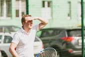 pic of early-man  - young man play tennis outdoor on tennis field at early morning - JPG