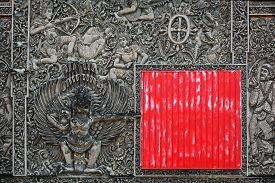 stock photo of garuda  - Ancient Balinese stone carving on the wall partially closed by red square shield with traditional characters of the Hindu religion and a symbol of Indonesia  - JPG
