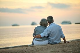 picture of maturity  - Happy Mature couple relaxing on beach at sunset - JPG
