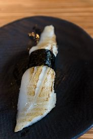 stock photo of halibut  - A piece of Halibut sushi on a black plate - JPG