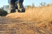 foto of stomp  - A person levitating in mid air above a dirt path - JPG