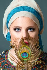 picture of female peacock  - Portrait of beautiful woman with blue eyes wearing turban and holding peacock feather - JPG