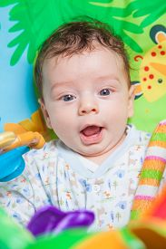 image of playmate  - 3 months old baby boy playing and learning on the playmat - JPG
