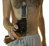 Cropped shot of a male hand holding a .38 calibre with a condom on it and hairy chest in the backgro