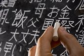 Close up of male hand writing Chinese and Japanese characters on blackboard. The words in Japanese h