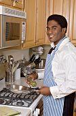 Handsome African-American businessman cooks dinner after work
