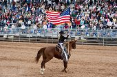 APACHE JUNCTION, AZ - FEBRUARY 27: A rodeo queen on horseback displays the American flag at the Lost
