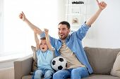 family, entertainment, sport and people concept - happy father and little son with ball watching foo poster