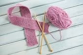 High angle view of pink woolen Breast Cancer Awareness ribbon with crochet needles on wooden table poster
