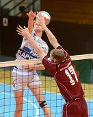 KAPOSVAR, HUNGARY - JANUARY 17: Krisztian Csoma (in white) blocks the ball at a Hungarian volleyball