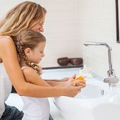 Mother and daughter washing their hands. Female with a child to wash their hands with soap and water poster