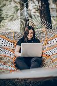 Beautiful Brunette Woman Relaxing On Hammock Outdoors Near Lake In The Forest, Freelancer Working In poster