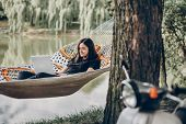 Young Female Freelancer Working On Laptop While Lying On A Hammock Near A Lake, Hipster Woman Restin poster