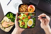 Man Eating Lunch From Takeaway Lunch Box At Working Table. poster