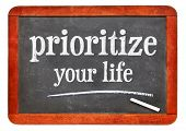 Prioritize your life advice - white chalk text on a isolated vintage slate blackboard poster