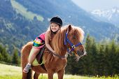 Kids Riding Pony In The Alps Mountains. Family Spring Vacation On Horse Ranch In Austria, Tirol. Chi poster