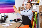 Man Designer And Print Operator With Paper Print At Print Manufacturing poster