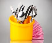 Kitchen cutlery, knives, forks and spoons in yellow stand with pink napkin on grey background