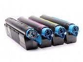 Four used laser printer toner cartridges of Cyan, Magenta, Yellow and black color shot over white ba