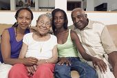 stock photo of mother law  - Couple sitting with their teenage daughter and mother in - JPG