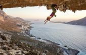 Female Rock Climber Hanging Upside Down On Challenging Route In Cave At Sunset, Resting Before Keepi poster