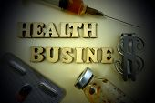Medical Concept. Inscription Health Business From Wooden Letters Next To A Pill, Syringe And Dollar  poster