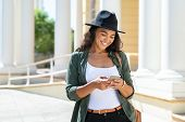 Cheerful young woman wearing black hat in city street typing a message. Hispanic trendy girl browsin poster