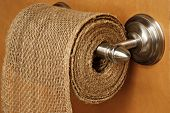 Humorous still life of rustic burlap on modern toilet paper dispenser with wood background.  Symbol