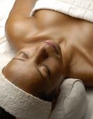 Beautiful young afro woman at beauty salon spa getting a body treatment. Beautiful young black woman