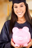 Graduate woman holding a piggybank with her education savings