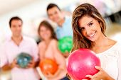 Beautiful woman bowling holding a ball with friends and smiling