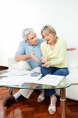 Senior couple with paperwork fighting over money at home