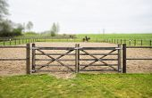 Wooden Gate To An Equine Training Course In A Misty Weather With Green Grass Around The Track poster