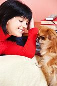 Smiled girl at home with her Pekingese dog
