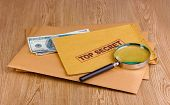 Envelopes with top secret stamp with magnifying glass and money on wooden background
