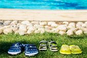 Three Pairs Of Beach Shoes Near Swimming Pool
