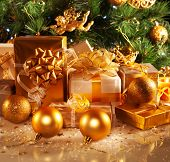 Photo of luxury gift boxes under Christmas tree, New Year home decorations, golden wrapping of Santa