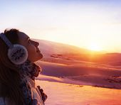 Photo of pretty woman walking in snowy mountains, side view of cute girl looking up, closeup portrai